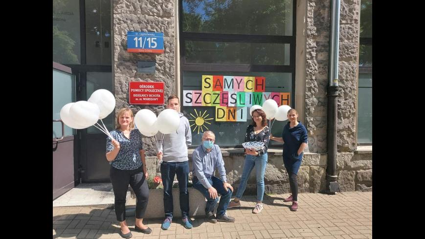 Trzy kobiety i dwóch mężczyzn z balonami przed wejsciem do budynku