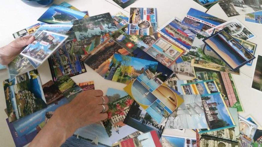 grafika: stół pełen pocztówek i zdjęć z różnych stron świata i różnymi widokami.